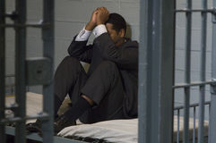 Businessman Sitting In Prison Cell Stock Photo