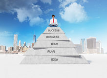 Businessman sitting on pyramid. Businessman sitting on business pyramid with laptop Royalty Free Stock Photography