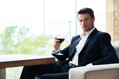 Businessman sitting at restaurant with glass of wine Stock Images