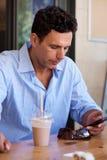 Businessman sitting at restaurant looking at mobile phone. Portrait of businessman sitting at restaurant looking at mobile phone Royalty Free Stock Photos