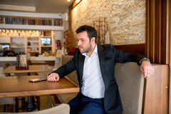Businessman is sitting in restaurant and waiting. Looking at his smartphone Stock Images