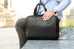 Businessman sitting / resting after working day and holding  a  leather briefcase in his hand Stock Photography