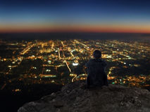 Businessman sitting on rocky mountain with city night view Stock Photography