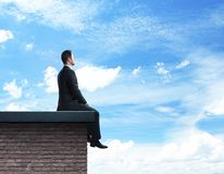 Businessman sitting on roof Stock Photography
