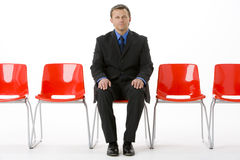 Businessman Sitting In Row Of Empty Chairs Stock Photography