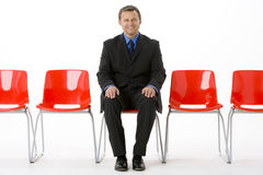 Businessman Sitting In Row Of Empty Chairs Royalty Free Stock Photo