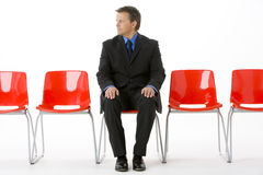 Businessman Sitting In Row Of Empty Chairs Royalty Free Stock Photography
