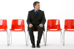 Businessman Sitting In Row Of Empty Chairs Royalty Free Stock Photos