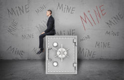 Businessman sitting on safe and background of wall with inscription `Mine`. Stock Photography