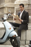 Businessman Sitting By Scooter Reading Newspaper Royalty Free Stock Photos