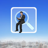 Businessman sitting on searching app icon using smart pad Stock Image