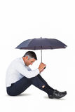 Businessman sitting and sheltering with umbrella Royalty Free Stock Photography