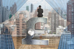 Businessman sitting on silver pound symbol with lock. Rear view of businessman sitting on silver pound symbol with lock stock images