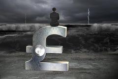 Businessman sitting on silver pound symbol with lock. Rear view of businessman sitting on silver pound symbol with lock, facing dark storm ocean and flooded royalty free stock image
