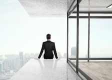 Businessman sitting on skyscrapper Royalty Free Stock Images