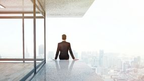 Businessman sitting on skyscrapper Stock Image