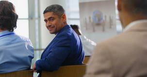 Businessman sitting and smiling in the business seminar 4k. Side view of a Caucasian businessman smiling to the camera and sitting in the business seminar 4k stock footage