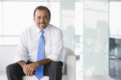 Businessman sitting on sofa in lobby Royalty Free Stock Photography