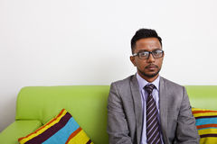 Businessman sitting on sofa looking at camera Stock Photos