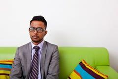 Businessman sitting on sofa looking at camera Royalty Free Stock Photos