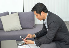 Businessman sitting at sofa and looking down at mobile phone scr Royalty Free Stock Photos