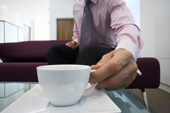Businessman sitting on sofa in office lobby, placing cup on coffee table, close-up, surface level Stock Image