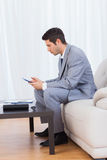 Businessman sitting on sofa texting message with his mobile Stock Images