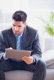 Businessman sitting on sofa using his tablet pc Stock Photos
