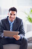 Businessman sitting on sofa using his tablet pc smiling at camera Royalty Free Stock Photography