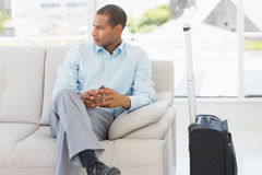 Businessman sitting on sofa waiting to depart on business trip Royalty Free Stock Images