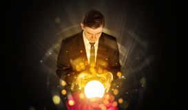 Businessman  sitting with sparkling magic ball Stock Photo