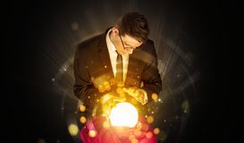 Businessman  sitting with sparkling magic ball stock image