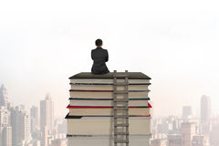 Businessman sitting on stack of books with wooden ladder Stock Photography