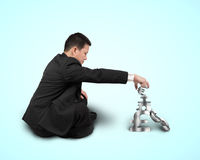 Businessman sitting and stacking sliver 3D symbols Royalty Free Stock Image