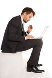Businessman sitting on a stair working on a laptop Stock Images
