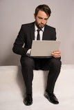 Businessman sitting on a stair working on a laptop Stock Photography