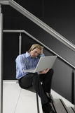 Businessman sitting on staircase, using laptop in lap, leaning head on hand, thinking, side view Royalty Free Stock Images