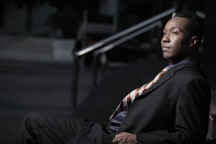 Businessman sitting on stairs at night. Young African American businessman sitting on a set of stairs outside at night Royalty Free Stock Photo