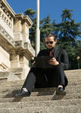Businessman sitting on stairs and watching his tablet Royalty Free Stock Photo