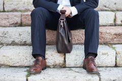 Businessman sitting on steps with his briefcase Stock Images