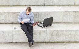 Businessman sitting on the steps and working with computer. Royalty Free Stock Images