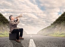 Businessman shouting with a megaphone. Businessman sitting on a suitcase shouting with a megaphone on a road Royalty Free Stock Photography