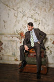 Businessman sitting on suitcases. Business trip. Stock Photos