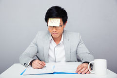 Businessman sitting at the table with adhesive note Stock Images