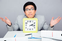 Businessman sitting at the table with big clock and shrugging Royalty Free Stock Photo