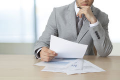 Businessman sitting table and holding document Stock Images