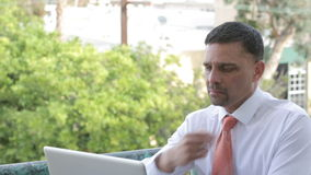 Businessman sitting on a table outdoors and working on the laptop stock footage