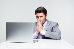 Businessman sitting at the table and praying Royalty Free Stock Image