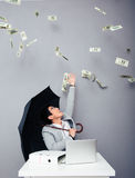 Businessman sitting at the table with rain of money Stock Photos