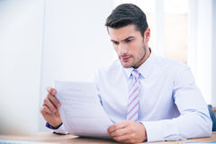 Businessman sitting at the table reading document Stock Photo